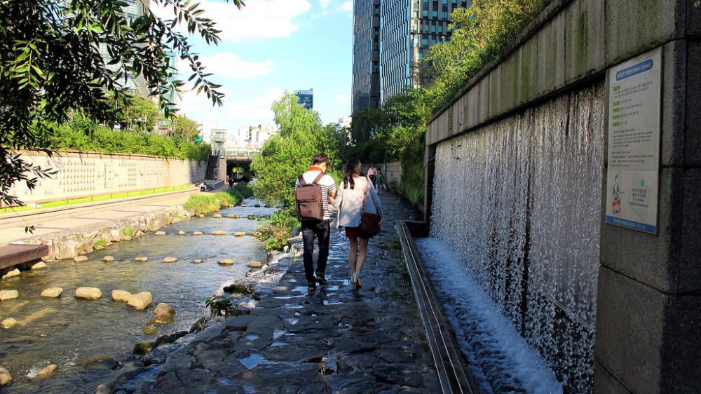 a couple walking down Cheonggyecheon